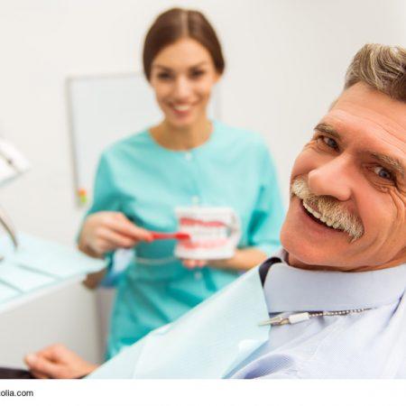 Mann und Zahnarzthelferin in der Zahnarztpraxis mit Zahnersatz und Pflege